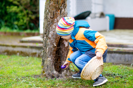 Cute adorable little kid boy making an egg hunt on Easter. Imagens
