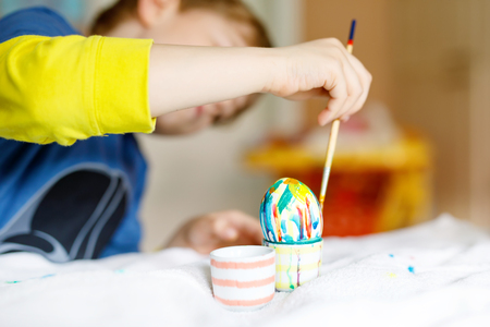 Close-up of little kid hands coloring eggs for Easter holiday Stock Photo