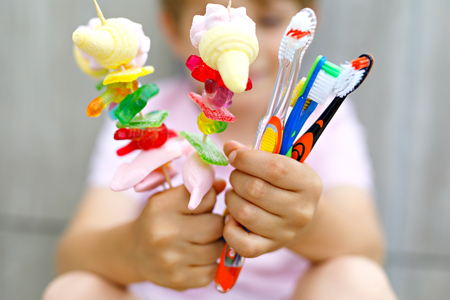 little kid boy holding marshmallow skewer in one hand and toothbrushes in another Stock Photo
