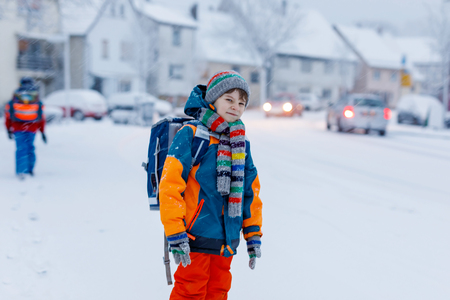Two little kids boys of elementary class walking to school during snowfall Foto de archivo