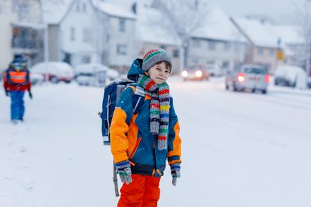 Two little kids boys of elementary class walking to school during snowfall Standard-Bild