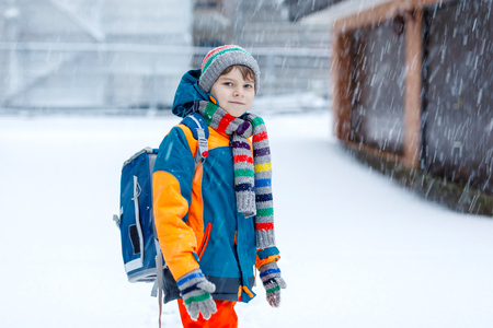 Happy kid boy having fun with snow on way to school Stok Fotoğraf