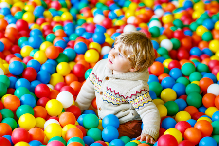 Little kid boy playing at colorful plastic balls playground