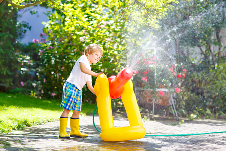 little kid boy playing with a garden hose water sprinkler