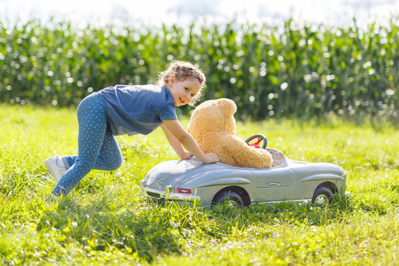 Little preschool kid girl driving big toy car and having fun with playing with big plush toy bear Stock Photo