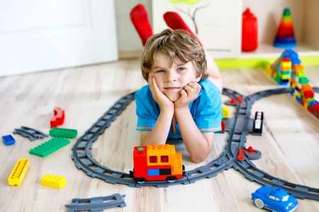 little blond kid boy playing with colorful plastic blocks and creating train station
