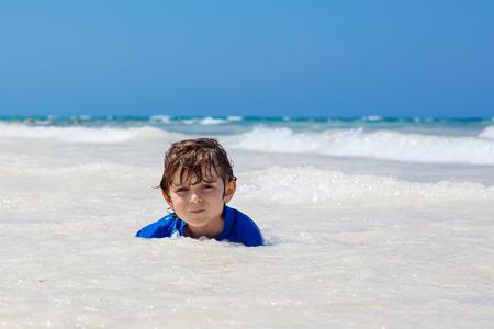 little blond kid boy having fun on tropical beach of Haiti Stock Photo