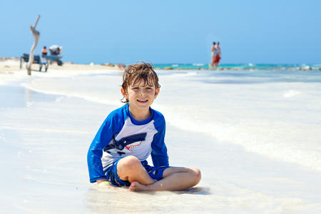 little blond kid boy having fun on tropical beach of Mexiko Stock Photo