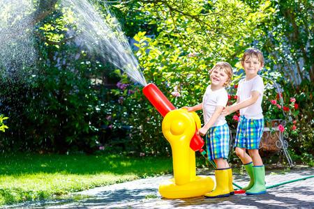 Dos niños pequeños jugando con un rociador de agua de rociadores de agua Foto de archivo - 95087879