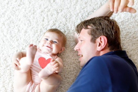 Happy proud young father with newborn baby daughter, family portrait togehter 写真素材