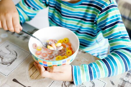 little blond school kid boy eating cereals with milk and berries, fresh strawberry for breakfast