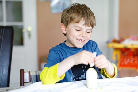 Little blond kid boy coloring eggs for Easter holiday in domestic kitchen, indoors. Stock Photo