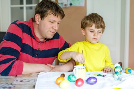 Little blond preschool kid boy and father coloring eggs for Easter holiday Stock Photo