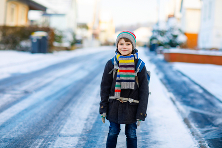 Happy kid boy with backpack or satchel having fun with snow on way to school