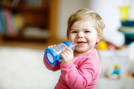 Cute adorable ewborn baby girl holding nursing bottle and drinking formula milk or water