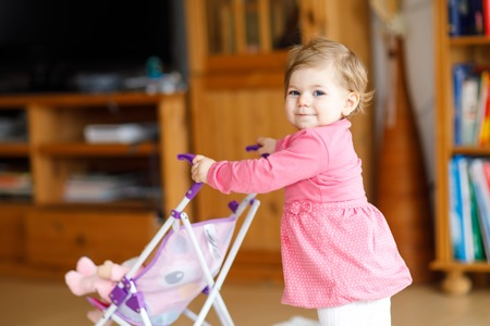 Cute adorable baby girl making first steps with doll carriage.