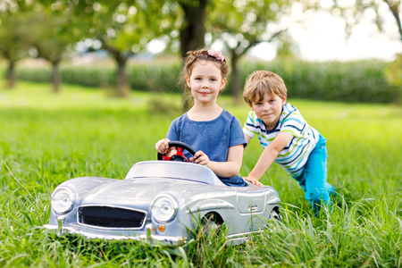Two happy children playing with big old toy car in summer garden, outdoor