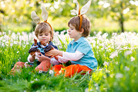 Two little boy friends in Easter bunny ears eating chocolate cakes and muffins Stock Photo