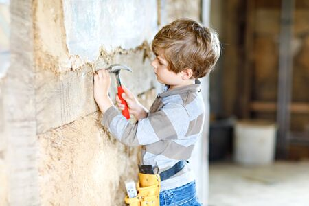 Little kid boy helping with toy tools on construciton site.