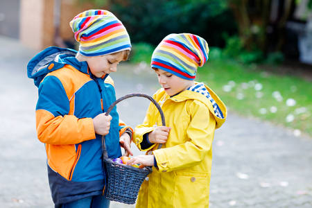 Two little kids boys and friends making traditional Easter egg hunt Stock Photo