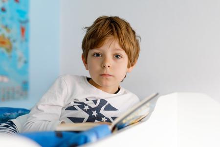 Cute blond little kid boy in pajamas reading book in his bedroom
