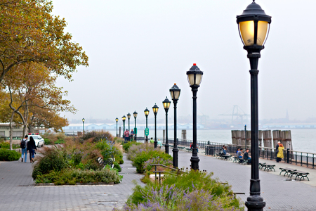 Seafront of New York city on day with heavy fog in autumn, Battery Park.