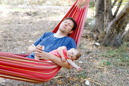 Cute adorable baby girl of 6 months and her father sleeping peaceful in hammock in outdoor garden