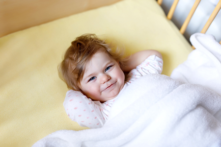 Cute little baby girl lying in cot before sleeping. Happy calm child in bed. Going sleep. Peaceful and smiling child
