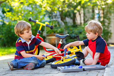Two happy little kid boys repair chain on bikes and change wheel of balance bicycle