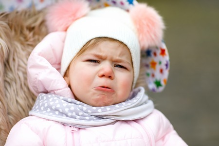 Sad crying hungry baby girl sitting in the pram or stroller on cold day Stock Photo