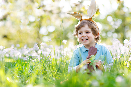 Cute little kid boy with Easter bunny ears celebrating traditional feast. Happy child eating chocolate rabbit fugure Stock Photo