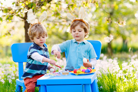 Two little boys wearing Easter bunny ears, painting colorful egg Stock Photo