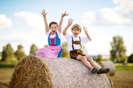 Two kids, boy and girl in traditional Bavarian costumes in wheat field with hay bales Standard-Bild - 96639165