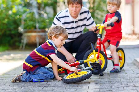 Two happy little kid boys and father repair chain on bikes and change wheel of balance bicycle