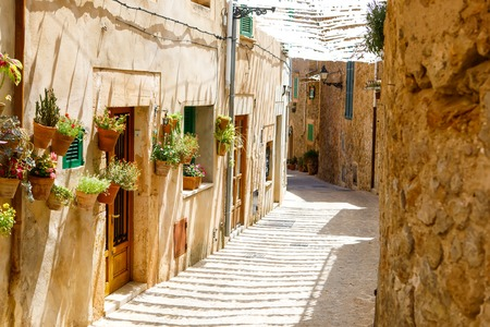 Beautiful street in Valldemossa with traditional flower decoration, famous old mediterranean village of Majorca. Balearic island Mallorca, Spain Фото со стока