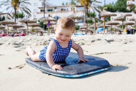 Portrait of cute little baby girl in swim suit on beach in summer.