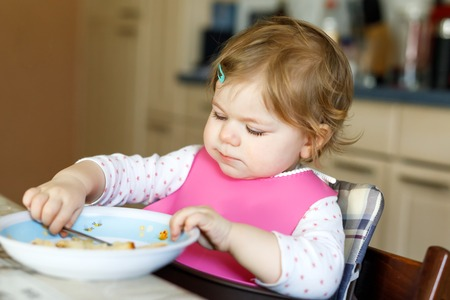 Adorable baby girl eating from spoon mashed vegetables and puree. food, child, feeding and people concept