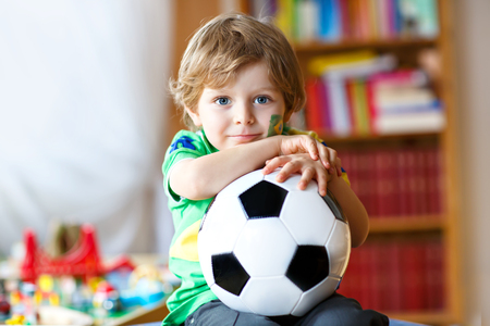 Little blond preschool kid boy with ball watching soccer football cup game on tv.