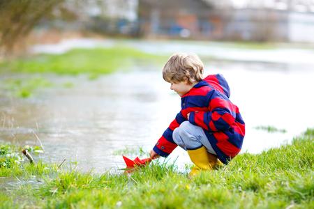 Gelukkig klein kind jongen in gele regenlaarzen spelen met papier schip boot door enorme plas op lente of herfst dag