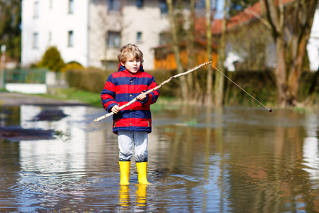 Little kid boy wearing yellow rain boots and walking and jumping into puddle on warm sunny spring day. Stock Photo
