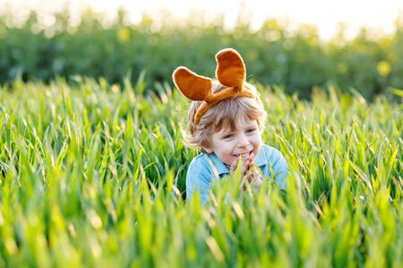 little kid boy having fun with traditional Easter egg hunt Stock Photo