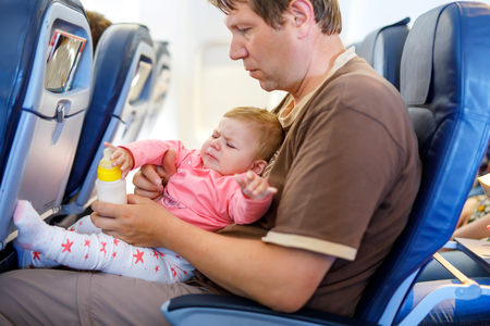 Young tired father and his crying baby daughter during flight on airplane going on vacations