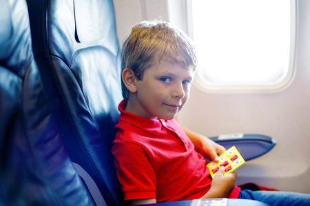 Little kid boy playing tic tac toe game during flight on airplane.