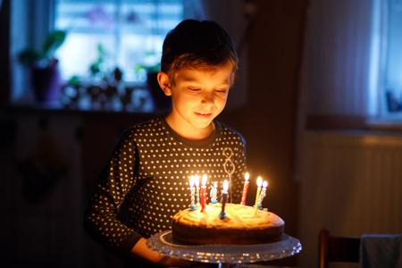 Adorable happy blond little kid boy celebrating his birthday.