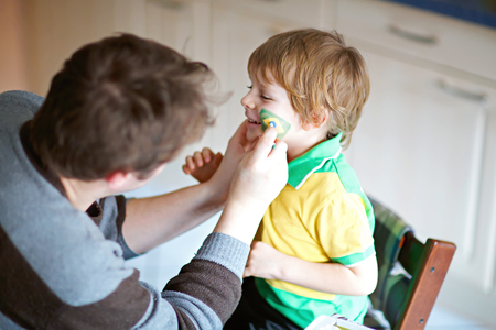 Young dad painting flag on face of little son for football or soccer game.