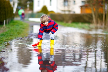 Happy little kid boy in yellow rain boots playing with paper ship boat by huge puddle on spring or autumn day