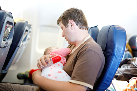 Young tired father and his baby daughter sleeping during flight on airplane going on vacations. Stock Photo