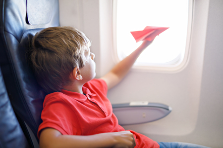 Little kid boy playing with red paper plane during flight on airplane. Banco de Imagens
