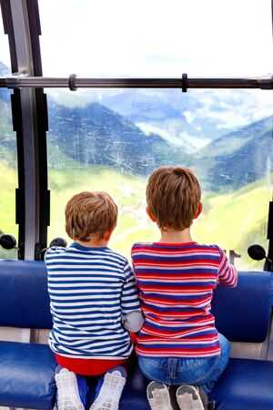Two little boys sitting inside of cabin of cable car and looking on mountains landscape. Banco de Imagens