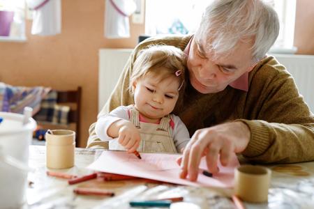 かわいい赤ちゃんの幼児の女の子と自宅でカラフルな鉛筆で絵を描くハンサムな先輩祖父。